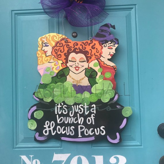 "Sanderson Sister Door Hanger made from wood and hanging from a big bow, this door hanger features the Sanderson sisters in a cauldron that says ""Just a Bunch of Hocus Pocus."