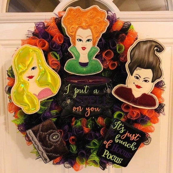 "Wreath featuring ruffled tulle and embroidered Hocus Pocus figures such as the Sanderson Sisters, Book , a Cauldron that says ""I put a spell on you"", and a sign that says ""it's just a bunch of Hocus Pocus"". Wreath by Colliebug Creations"