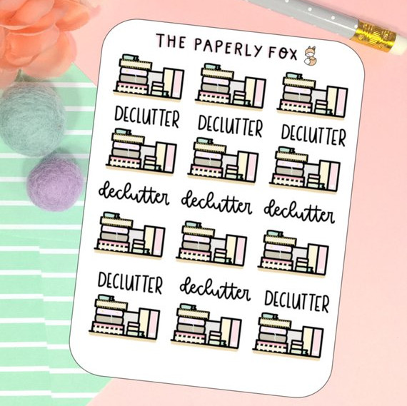 Declutter planner stickers featuring stacked boxes and books and the words declutter in different fonts